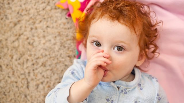 Red Haired Little Girl Laying on Floor Sucking Thumb